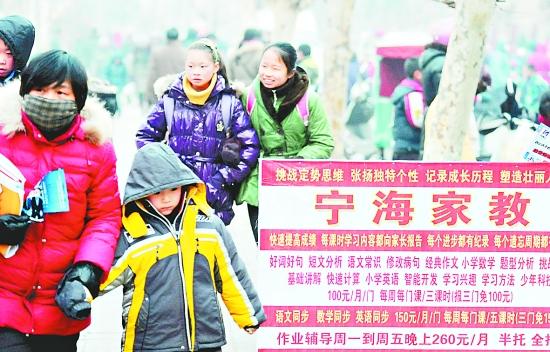 1月25日,学生和家长从江苏省连云港市街头的家教广告牌旁走过。   目前,连云港市各类培训班、辅导班、家教班等已早早打出广告开始招生,假期逐渐成为第三学期。   是谁动了孩子们的寒假?   新华社发